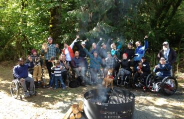 group of Oregon SCI members posing for a photo next to campfire