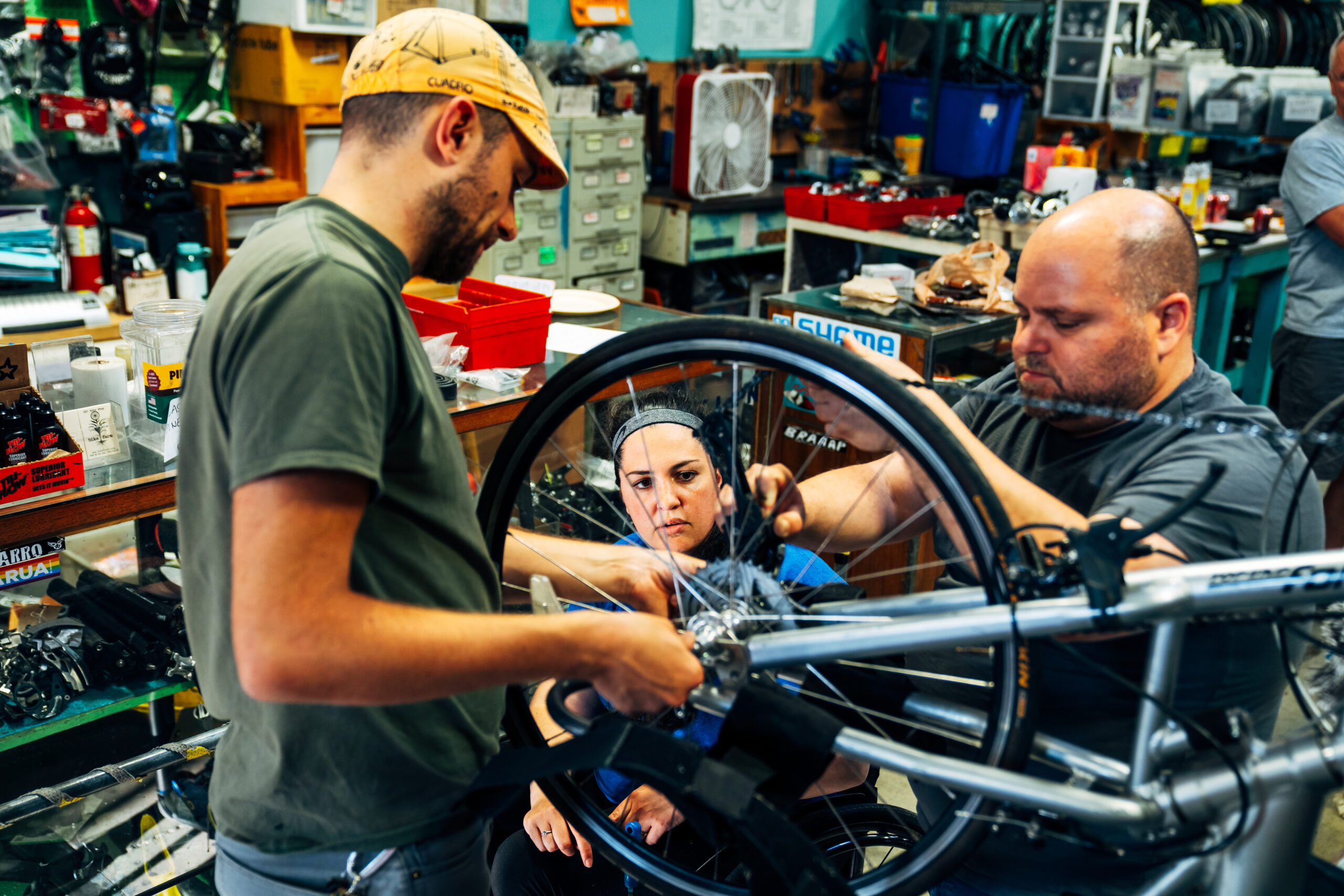 two men and a woman in a wheelchair fixing a tire